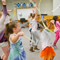 image of children dancing with ribbons indoors
