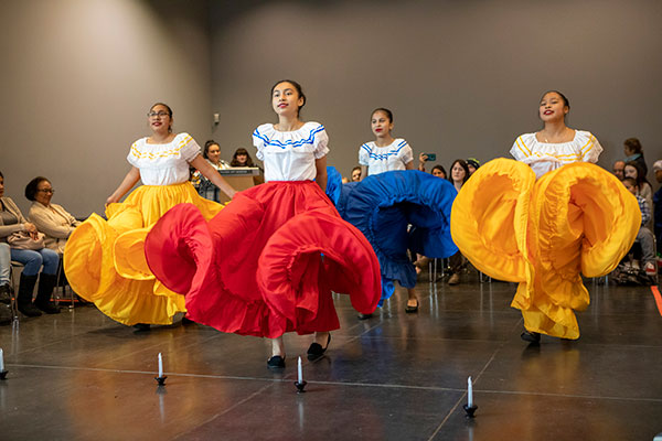Female students in colorful skirts dancing