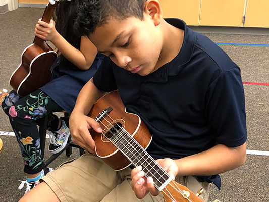 Young male student playing a ukelele